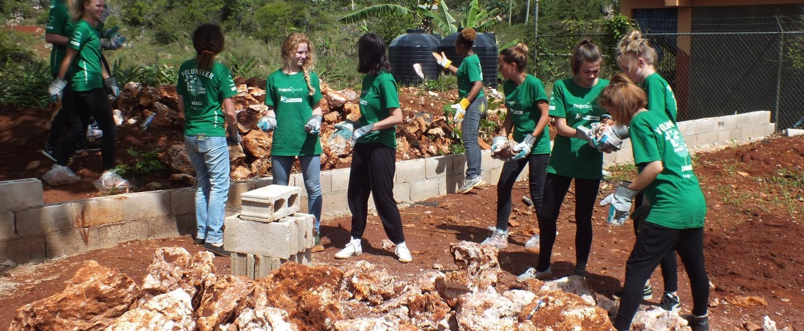 A group of people clear ground for a new playground at a disadvantaged school during their short-term volunteer abroad trip to Jamaica.